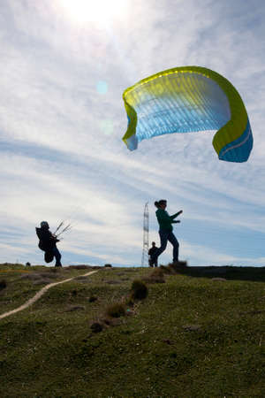 man trying to control the paraglide with friends and an antenna