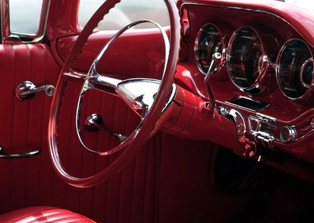 Red 1950s classic car interior, with steering wheel and instrument panel (focus on steering wheel).