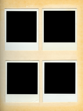 Four blank instant photo frames mounted on a retro photo album page Imagens