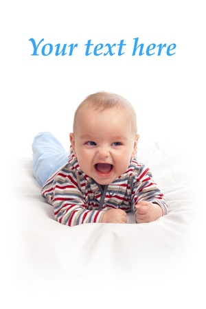 Happy baby boy on white blanket, studio shoot