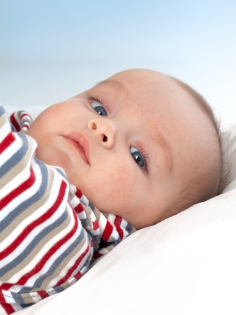Cute baby boy looking at camera, blue background