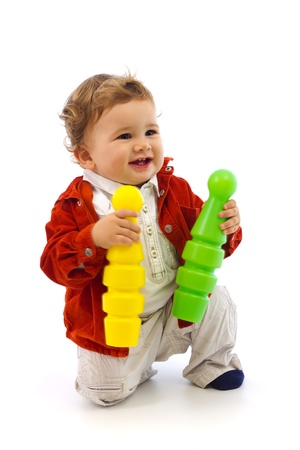 Little baby boy playing with red and green skittles Stock Photo