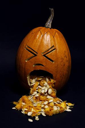 Halloween pumpkin, throwing up, isolated over  dark background
