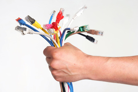 Holding a  Bunch of different colored ethernet cords over a white background