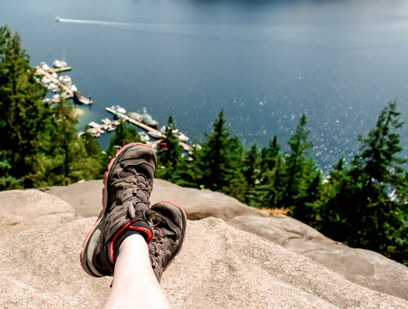 cross legs: hiker sitting on a mountain, legs crossed, enjoying the view