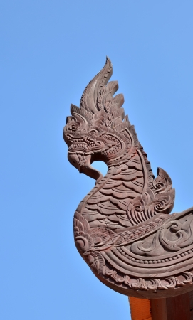 Wood carved serpent on blue sky background photo