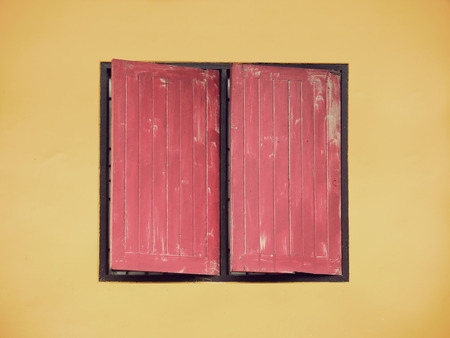 red wood window on yellow cement wall in vintage style photo