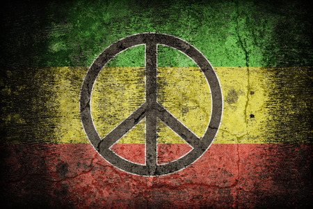 rastafari: Rasta flag pattern with a peace on dirty old concrete wall texture ,retro vintage style