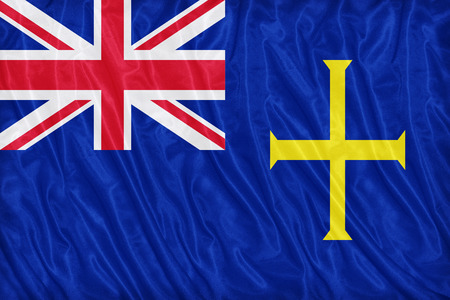 ensign: State Ensign of Guernsey flag pattern on the fabric texture ,vintage style Stock Photo