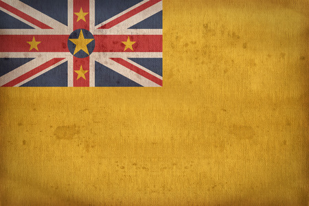 Niue flag pattern on fabric texture,retro vintage style Stock Photo
