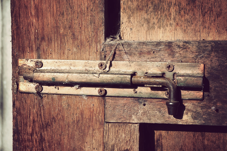 door bolt: The old dirty bolt at the wooden door, retro vintage style