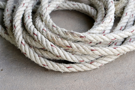 loopable: close up coil of old rope on concrete ground Stock Photo