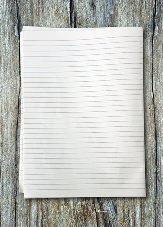 white lined sheet of notepad paper on old wooden
