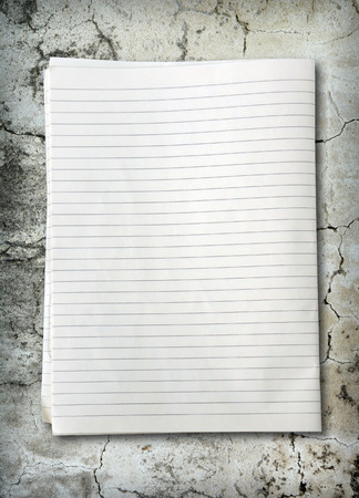 college ruled: white lined sheet of notepad paper on dirty concrete