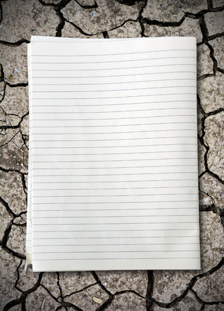 college ruled: white lined sheet of notepad paper on crack soil