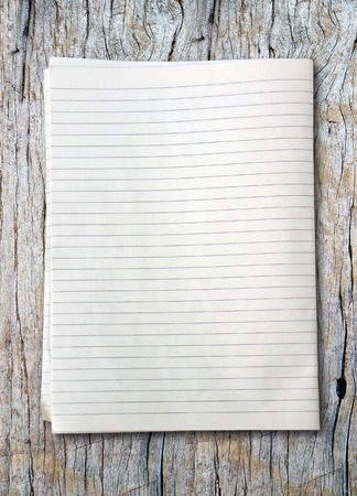 college ruled: white lined sheet of notepad paper on old wooden