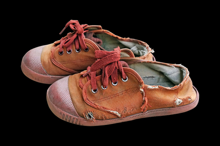old and dirdy brown canvas students shoes on black background Stock Photo