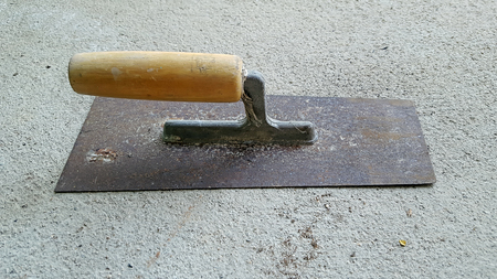rusty and dirty trowel plastering on cement floor Stock Photo