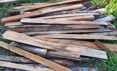 Pile of old timber planks from wood mill Imagens