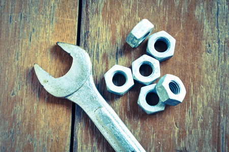 antecedents: wrench tool and nut on wood