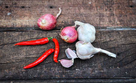 antecedents: Shallots (red onion), garlics and red chilli set up on wood