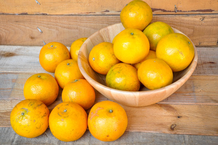 antecedents: Oranges in wooden bowl Stock Photo