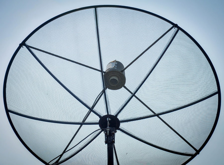 wireles: A satellite dish on the roof with blue cloud sky. Stock Photo