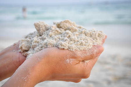Sand carried in the hand of the girl. Stock Photo
