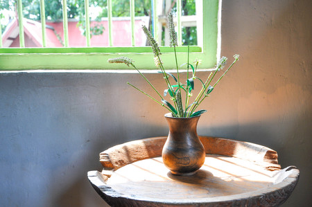 Vintage wooden vase on a table by the window.