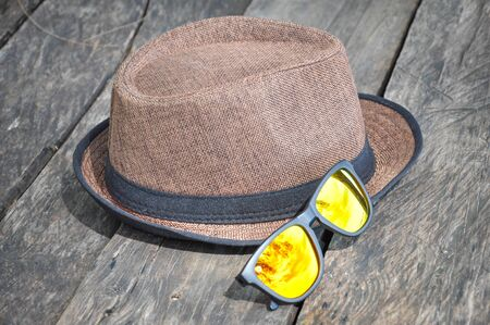 Hat and sunglasses are placed on old wooden boards