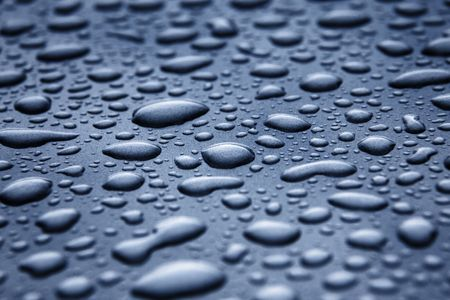 Beads of water on a blue-grey metallic surface photo