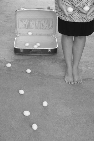 ovarios: imagen en blanco y negro mujer de la celebraci�n de dos huevos junto a abrir la maleta llena de huevos
