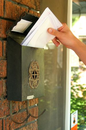 close-up of hand getting mail from mailbox. Stock Photo