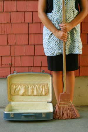 color image of woman holding a broom next to an open suitcase.