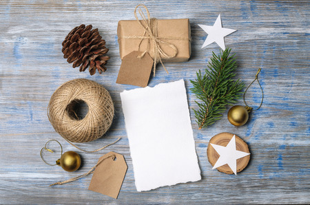 Christmas background. Holiday decorations: gifts, cones, stars, balls on wooden table. Paper with space for writing. Top view.