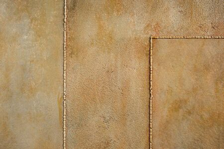 Textured rusty metal background. Decorative plaster. Interior wall decoration. Imitation of an old wall close-up.
