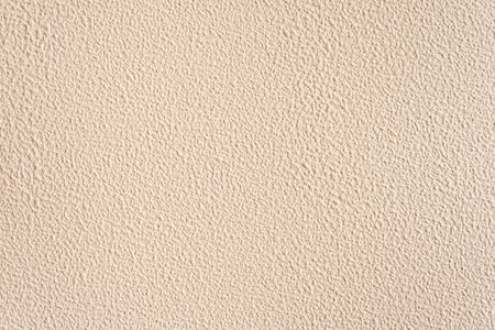 Textured nude background. Decorative plastering, external decoration of the facade. Background image of a wall with beige rough coating.