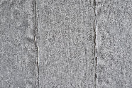 Textured gray background. Decorative concrete plaster imitates the imprint of a wooden board. Exterior decoration of the facade close-up. 免版税图像