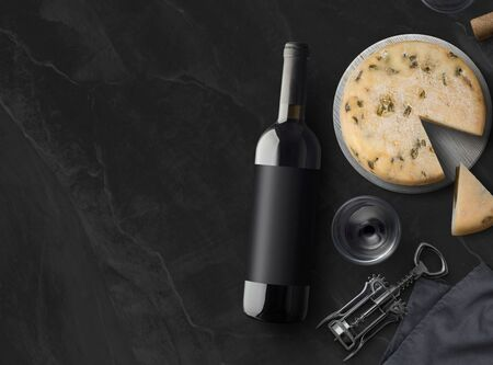 Red Wine bottle, corkscrew, wineglass, cheese on black stone background, top view, copy space. Wine bottle mockup. Top view. 免版税图像
