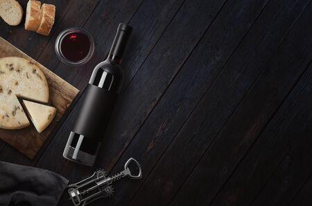Red Wine bottle, corkscrew, cheese, wineglass, bread on black wood background, top view, copy space. Wine bottle mockup. Top view. 免版税图像