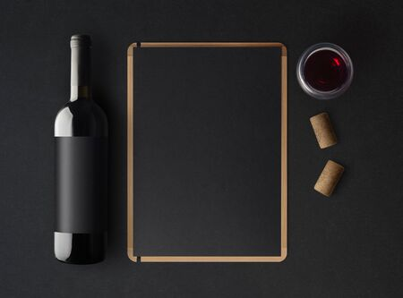 Bottle of red wine with a black label on a dark background, a wine menu template and a glass of wine. Mockup. Top view. 免版税图像