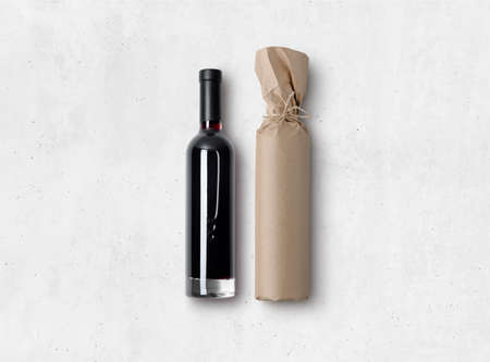 Mock-up of a bottle of red wine and bottle wrapped in craft paper on concrete background. Blank objects for placing your design. 3d illustration.
