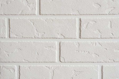 Textured white background. Decorative concrete coating imitating a brick wall. Textured wall plaster, exterior facade.