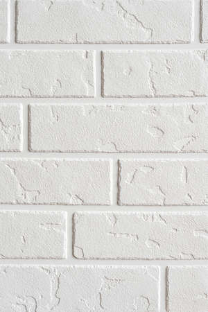 Textured white background vertical. Decorative concrete coating imitating a brick wall. Textured wall plaster, exterior facade.