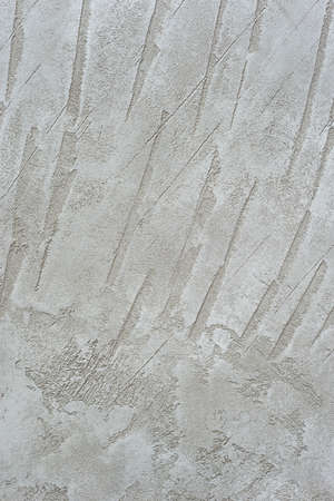 Textured vertical background. Decorative gray plaster imitating an old concrete wall. Exterior cement facade finish.