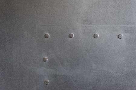 Textured gray background horizontal. Decorative plaster imitating a metal surface. Interior wall decoration close-up.