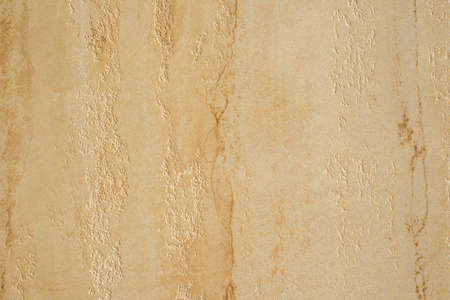 Textured concrete background. Decorative wall plaster, interior decoration. Beige decorative coating with vertical strokes. 免版税图像