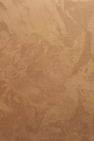 Textured vertical background. Decorative gold plaster imitating a vintage wall. Background image of a textured wall.