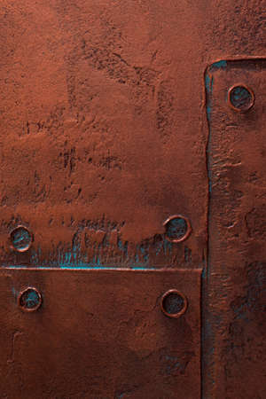 Textured vertical background. Decorative plaster imitates a rusty metal coating. Interior wall decoration close-up. 免版税图像