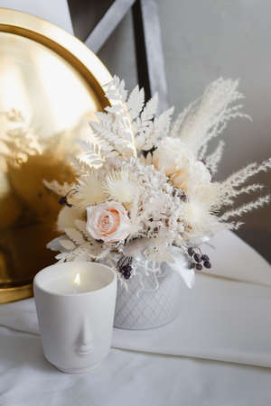Stylish composition of preserved flowers and dried flowers in a light color scheme on the background of a golden tray with a burning candle. Photo of a bouquet with roses in the interior. 免版税图像